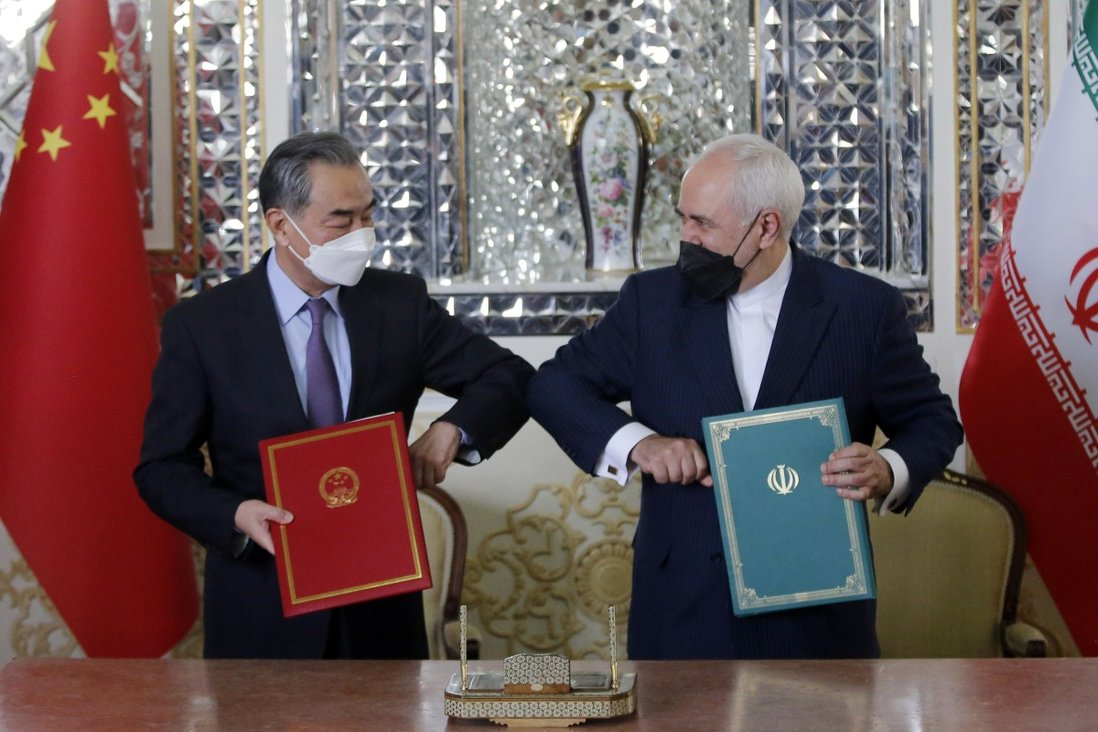 Iranian Foreign Minister Mohammad Javad Zarif (right) greets Chinese Foreign Minister Wang Yi after a document-signing ceremony in Tehran on March 27. Photo: EPA-EFE