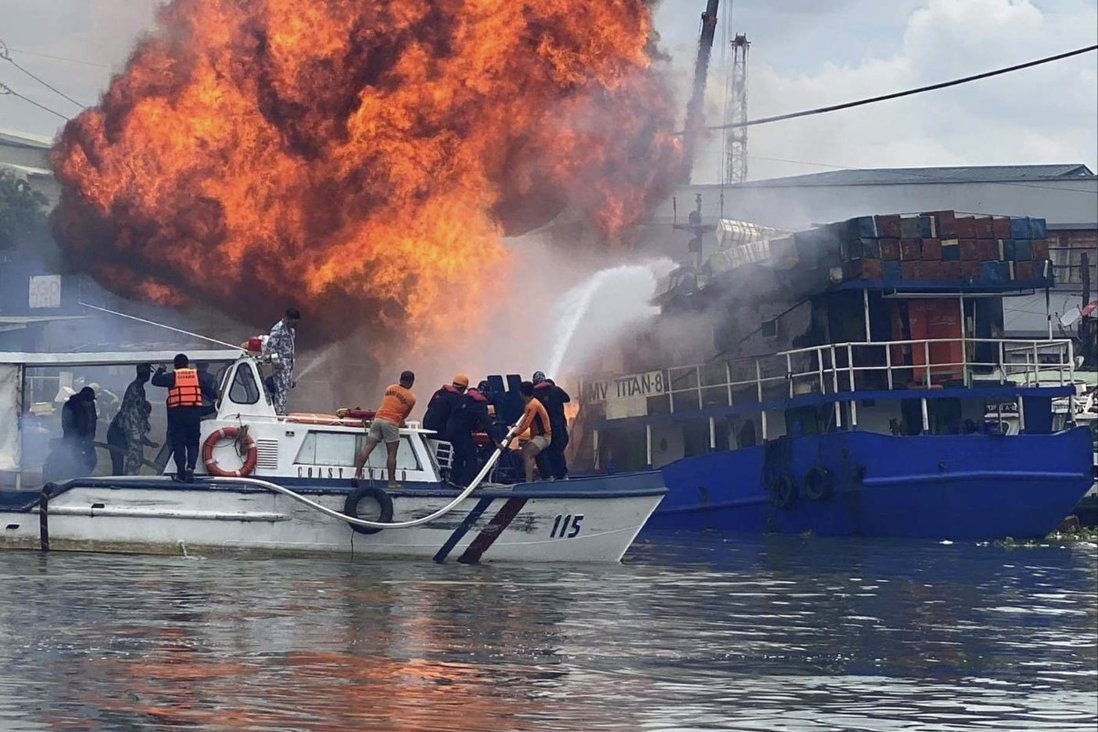 Members of the Philippine Coast Guard try to extinguish flames on a burning cargo ship docked in Manila on Saturday, June 12. Photo: AP