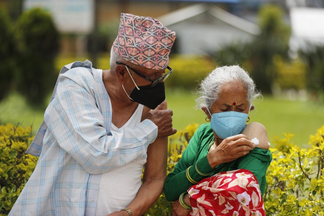 An elderly Nepalese couple wait outside after receiving a Covid-19 vaccine in Kathmandu, Nepal, on August 9. Photo: AP