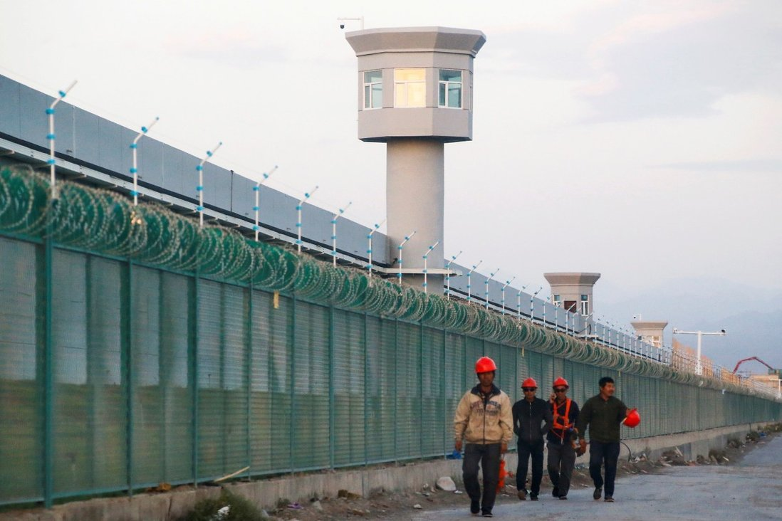 Workers walking by the perimeter fence of what is officially known as a vocational skills education centre in Dabancheng in Xinjiang Uygur autonomous region. According to the Committee to Protect Journalists, about half the reporters in jail in China this year are Uygurs from the region. Photo: Reuters
