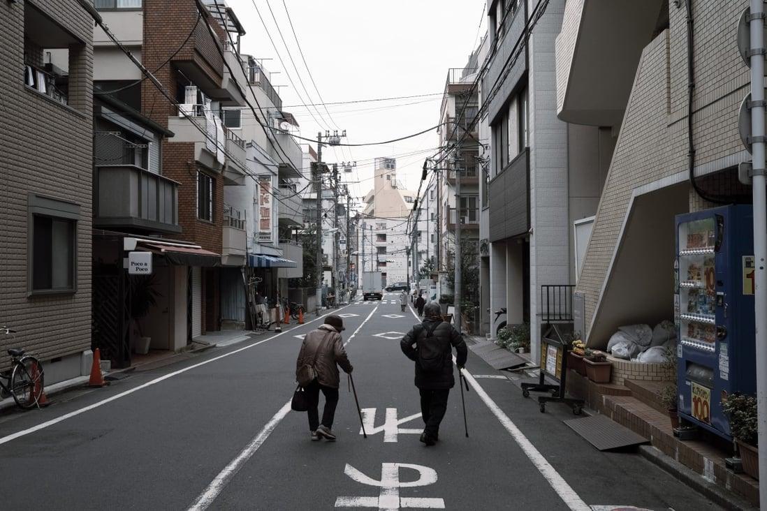 Ältere Bewohner gehen eine Straße im Stadtteil Toshima in Tokio entlang. Foto: Bloomberg