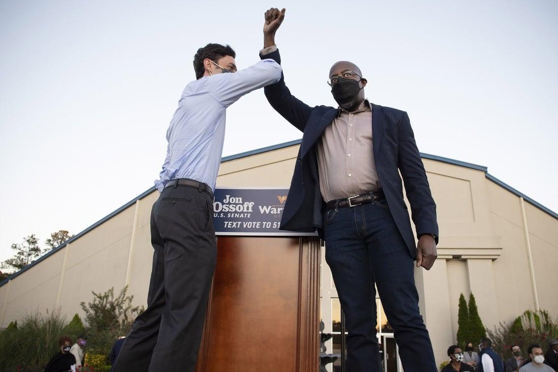 Democratic candidates Jon Ossoff, left, and Raphael Warnock bump elbows on stage at a rally in Jonesboro, Georgia on November 19. Photo: Zuma Press via TNS