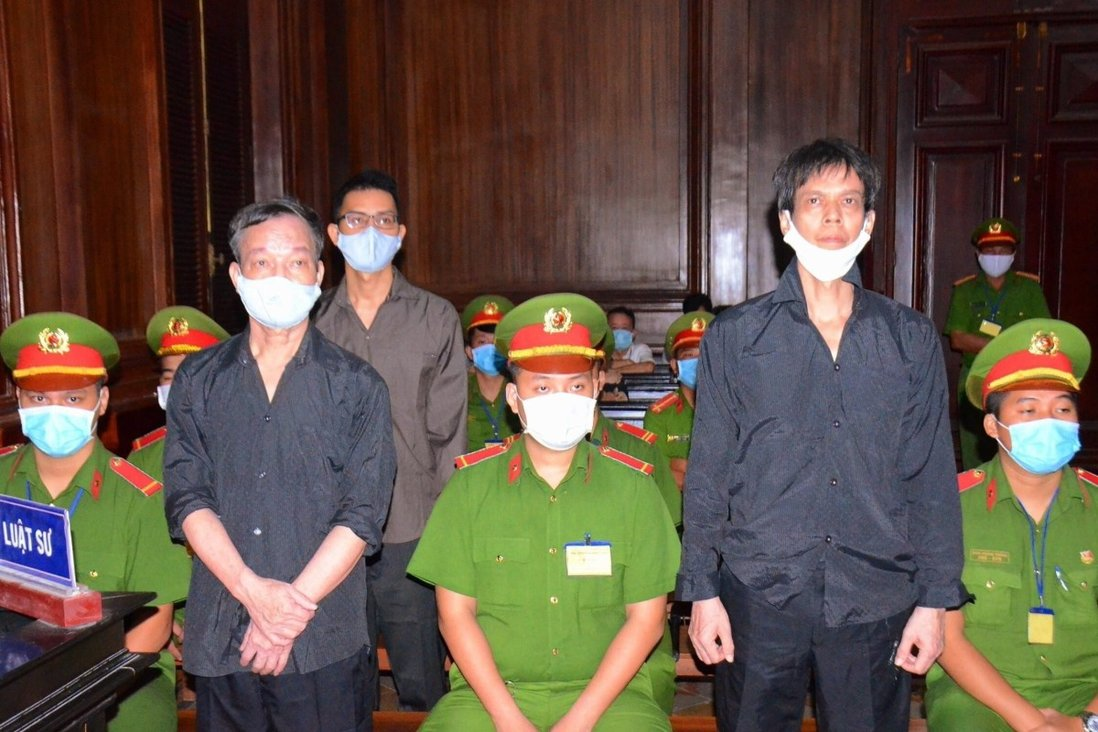 Vietnamese journalists Pham Chi Dung, right, Le Huu Minh Tuan, centre back, and Nguyen Tuong Thuy, left, stand between police during their trial in Ho Chi Minh City. Photo: EPA