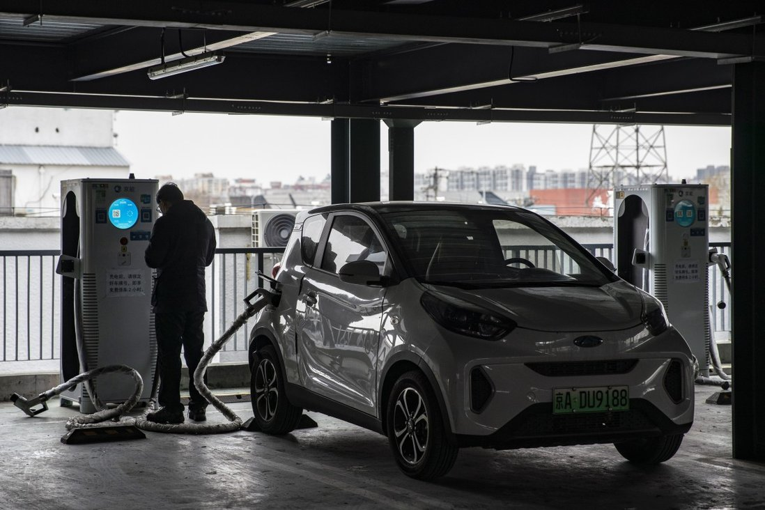 A man charges his electric car in Beijing. Photo: Bloomberg