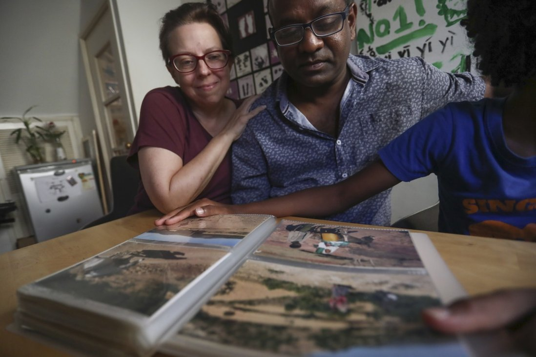 Karen Arndt (left) and Chris Prosper, with their 10-year-old son, who was adopted from Ethiopia's Tigray region, look through their photo album, in their home in Shek O. Photo: Jonathan Wong
