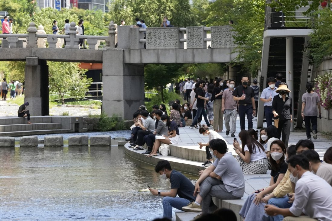 People sit at the Cheonggye Stream in Seoul. About 42.6 per cent of South Koreans are fully vaccinated. Photo: AP