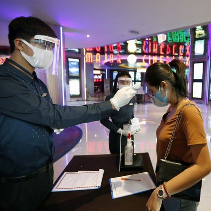 Cinema patrons get their body temperature checked as part of Covid-19 screening. Design changes to entertainment premises are needed in the long run to fight the virus. Photo: EPA-EFE