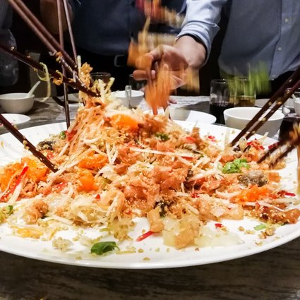 Yee sang salad being tossed during Lunar New Year. Photo: Shutterstock